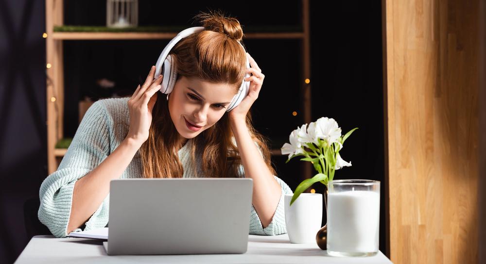 Womaninheadphoneswatchingwebinaronlaptopincafe