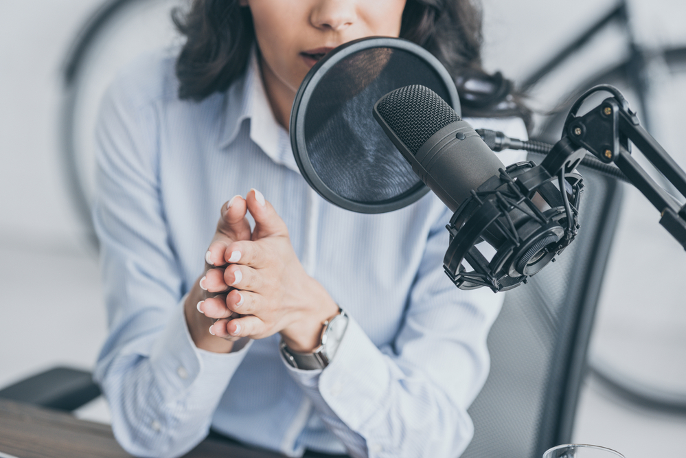 cropped-shot-of-radio-host-speaking-in-microphone-